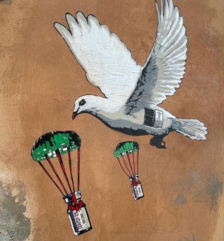 Street art, una colomba porta vaccini al Ministero della Salute
