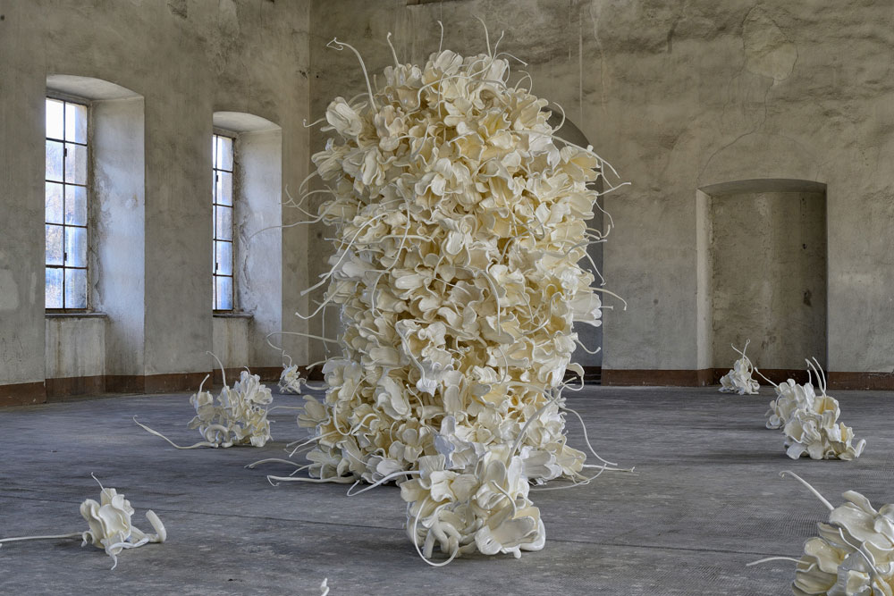 Biella, Cracking Art porta una grande installazione di 400 fiori di plastica in un'azienda tessile